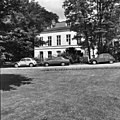 Rechter zijgevel met symmetrische indeling, ramen met roedeverdeling, twee dakkapellen. Geparkeerde auto's en bomen op de voorgrond - Baarn - 20397996 - RCE.jpg