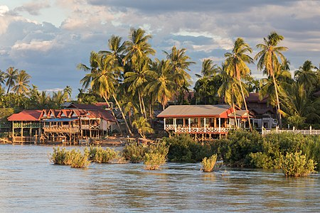 River bank of Don Khon with stilt wooden houses at golden hour from Don Det Laos