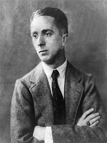 A black-and-white portrait photo of a young Norman Rockwell with his arms crossed in a light suit coat with a dark tie and white shirt