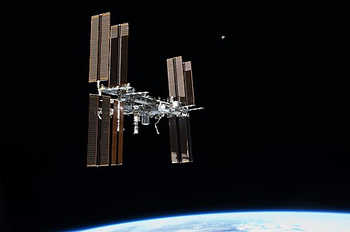 Photograph from the space shuttle Atlantis (STS-135) in its final fly-around of the International Space Station in July 19, 2011. Shows the ISS, Earth and moon.