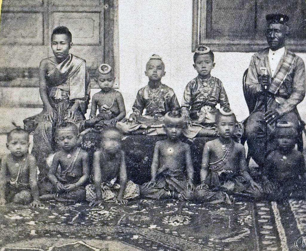 Sepia tinted photo of seated woman and older man separated by three children sitting on a bench, with several children sitting on the floor in front of them