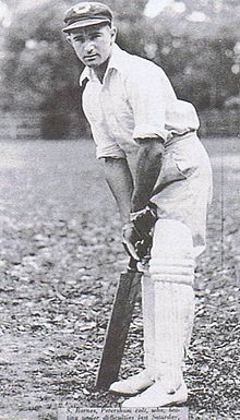 A teenage boy leans over his bat, in front of the stumps, in readiness to face a ball. He is wearing a white shirt, trousers and a cap.