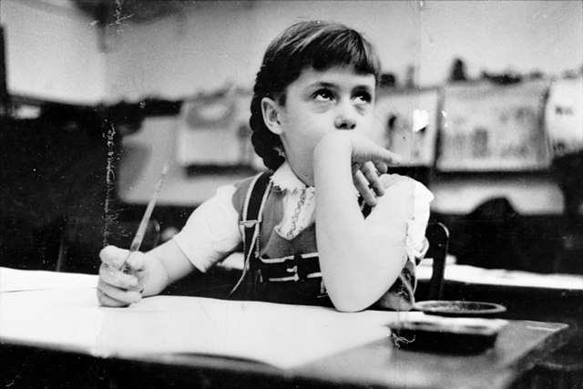 Young girl seated at desk in classroom in Chicago, Illinois. Image from Look photographic assignment with title: Chicago city of contrasts. Date	1949
