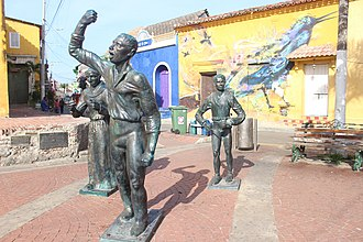 A view of the Colonial and traditional neighbourhood of Getsemani, usually found old houses painted with graffiti. Statues in Plaza de la Trinidad.jpg