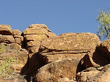 Engravings of animals and people adorn the vertical face of a rock formation.