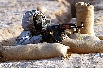 Syrian Armed Forces - A Syrian soldier aims a Type 56 assault rifle from his position in a foxhole during a firepower demonstration, part of Operation Desert Shield. The soldier is wearing a Soviet-made Model ShMS nuclear-biological-chemical warfare mask.