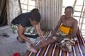 Tanzanian getting his leg examined (LF).png