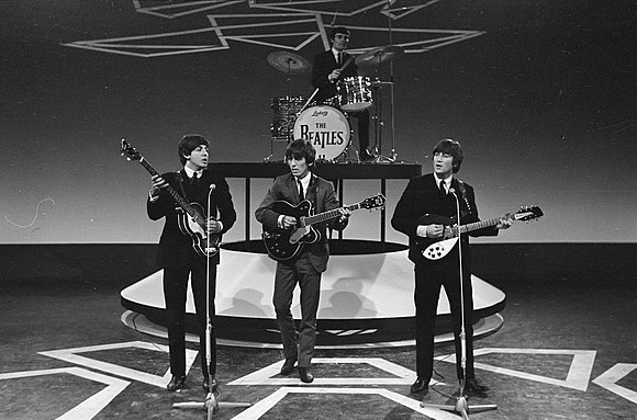 Lennon (right) performing in 1964 at the height of Beatlemania Televisie-optreden van The Beatles in Treslong te Hillegom vlnr. Paul McCartney, Bestanddeelnr 916-5099.jpg