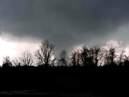 Tornado in Mississippi, located in Dixie Alley, obscured by trees and featuring a notably low, rugged base. Tornado in Mississippi on December 23, 2015.jpg