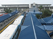 A commuter train station with blue roofs featuring a large train on one of the tracks.  A connecting elevated metro station is in the background.