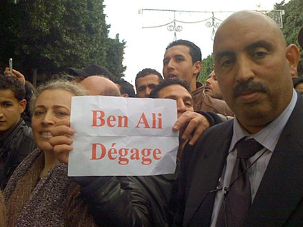 "Protesters with a sign that says ""Ben Ali, get lost"" in French. Tunisia Unrest - VOA - Tunis 14 Jan 2011 (3).jpg"
