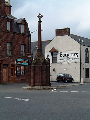 Turriff - Turriff mercat cross. The local red sandstone used in the cross and the buildings behind it is characteristic of Turriff's older buildings.