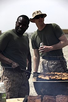 Two men in identical short-sleeved shirts and camouflage pants, one very dark-skinned with no hat and one very light-skinned wearing a hat and sunglasses, stand smiling over a barbecue full of cooking meat in a bright location.
