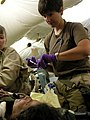 US Navy 030414-N-0728B-002 Ensign Jill Skeet from Williamsburg, Kan., administers pain medication to an unidentified Iraqi woman who arrived in Fleet Hospital Three's (FH-3) Casualty Receiving room with a gunshot wound.jpg