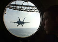 US Navy 040410-N-4953E-001 Airman Eric Johnson, assigned to Air Department's V-2 Division aboard USS Harry S. Truman (CVN 75), watches an aircraft take off of the flight deck from a forward porthole on the ship's bow.jpg