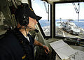 US Navy 060412-N-7981E-132 Ensign Justin Hall makes status reports to the bridge while standing watch as Helicopter Control Officer.jpg