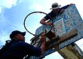 US Navy 061026-N-4399G-226 Boatswain's Mate 2nd Class Gerren Tyrese Alexander and Chief Warrant Officer Jeff Edward McElhannon fix a basketball rim at the Pasobolong Elementary School recess yard.jpg