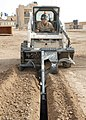 US Navy 070515-N-3560G-005 Equipment Operator 3rd Class Stephen Dixson of Naval Mobile Construction Battalion (NMCB) 4 digs a telephone line trench using a Bobcat trencher.jpg