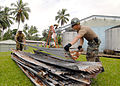 US Navy 070808-N-4267W-006 Steel Worker 3rd Class Doug Horrox attached to Naval Mobile Construction Battalion (NMCB) 7, and a member of the Papua New Guinea Defense Force (PNGDF) carry roofing.jpg