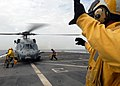 US Navy 090123-N-6278K-342 Aviation Boatswain's Mate (Handling) 1st Class Jaime Valencia directs personnel to chock and chain an HH-60H Seahawk helicopter.jpg