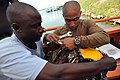 US Navy 090326-N-5242D-028 uganda Peoples Defense Air Force Lt. Robert Kijjali and Navy Diver 3rd Class Alberto Alejo remove the air supply from an umbilical used during surface-supply diving.jpg