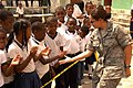 US Navy 090612-A-0868C-001 Capt. Christina Moore-Urrutia, commander of the U.S. Air Force South Band, shakes hands with students at the Santander Escuela during a Continuing Promise 2009 medical civic action program.jpg