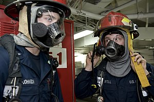 US Navy 111220-N-VO377-248 Sailors dress in full firefighting ensembles prior to battling a simulated fire during a general quarters drill aboard t.jpg