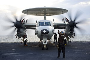 US Navy 120213-N-JN664-083 A plane captain relays hand signals between maintainers and pilots of an E-2C Hawkeye assigned to the Sun Kings of Airbo.jpg