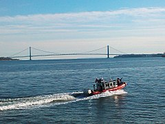 United States Coast Guard on patrol in Upper New York Bay. The Verrazano-Narrows Bridge across the Narrows is visible in the background.