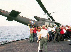 Lawrence Chambers - A South Vietnamese air force UH-1H is pushed overboard to make room for Major Buang to land his Cessna O-1.