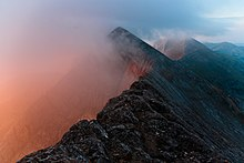 a series of jagged mountain peaks with a pinkish fog rising on the left side