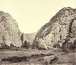A 19th-century monochrome photograph of a rocky river canyon, with sharp high cliffs in the background.
