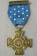 Front of a bronze cross-shaped medal hanging from a blue ribbon
