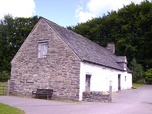 Dartmoor longhouse - A 1735 Welsh longhouse in the 'Dartmoor' style; the gable end drain can just be made out below the modern bench