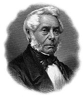 A white-haired man in a suit and bowtie faces the right.