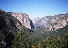 A glacial-carved valley filled with evergreen trees has a hanging valley and waterfall on the right and high cliff face on the left.