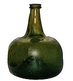 A squat semi-transparent green blown glass bottle, shaped vaguely like a squarish mandarin citrus, with a strongly concave base and a short flanged neck.