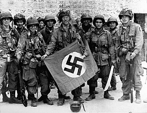 History of the 101st Airborne Division - 101st Airborne troops posing with a captured Nazi vehicle air identification sign two days after landing at Normandy.