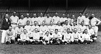 A posed team photo of a baseball team. They wear uniforms and are seated and standing in three rows, with a man in a jacket standing to the left.