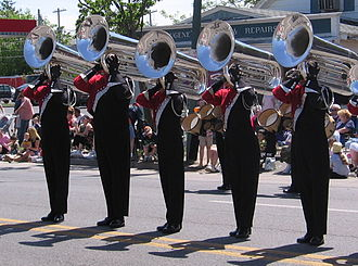Drum and bugle corps (modern) - The lowest-pitched of the horns used in drum corps is the contrabass bugle, or 'contra'. Here, members of a DCA corps from Upstate New York are shown performing in a parade.