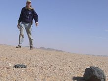 Low angle picture from ground showing sand and a large rock with a man looming a few feet back against a blue sky.