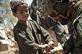 A U.S. Marine, right, with a Marine special operations team helps an Afghan boy tie off a sandbag during a construction project for an Afghan Local Police (ALP) checkpoint in Helmand province, Afghanistan 130330-M-BO337-077.jpg