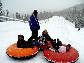 Tubing (recreation) - Adventure Point at Keystone Resort. The operator looks to ensure the people below clear the run safely before launching this family down one of the highest tubing hills sitting at 11,640 ft. On the left is their state of the art magic carpet used to deliver the tubers back up the run from the bottom.