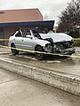 A now roofless damaged car displayed at the school .jpeg
