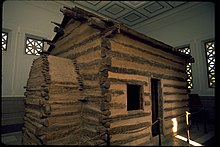 A log house on display inside a larger building.