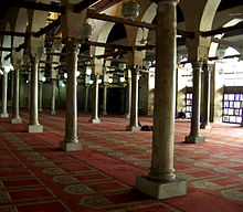 A large room filled with rows of cylindrical columns on top of square bases. The columns support arches which are pierced by square beams going the length of the room in both directions. Hanging from the beams are lamps, and the room's floor is covered with a red carpet with a repeated beige arched doorway shaped design on it. Exterior light enters from right of the room.