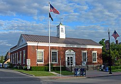 "A low brick building with a square cupola in the middle of its metal roof. Wording on the front says ""UNITED STATES POST OFFICE"" and ""ALBION NEW YORK"". There is an American flag flying from a flagpole in front and hanging from a lamppost on the right."