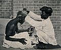 An amateur barber dressing a man's hair in a street. Process Wellcome V0019799.jpg