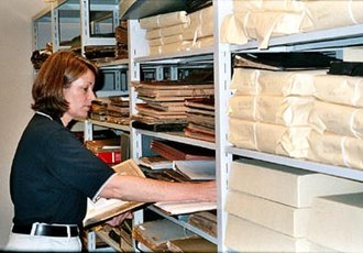 Archivist - An archivist surveying an unprocessed collection of materials. Surveying is commonly done to determine priorities for preservation and/or conservation of materials before an archivist begins arrangement and description.