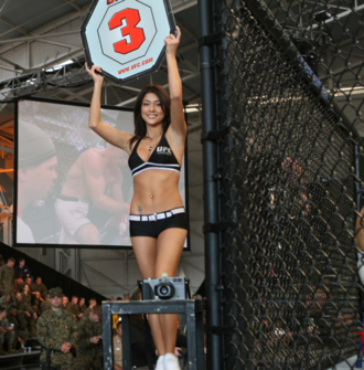Ring girl - UFC ring girl Arianny Celeste indicates that the third round is about to begin.